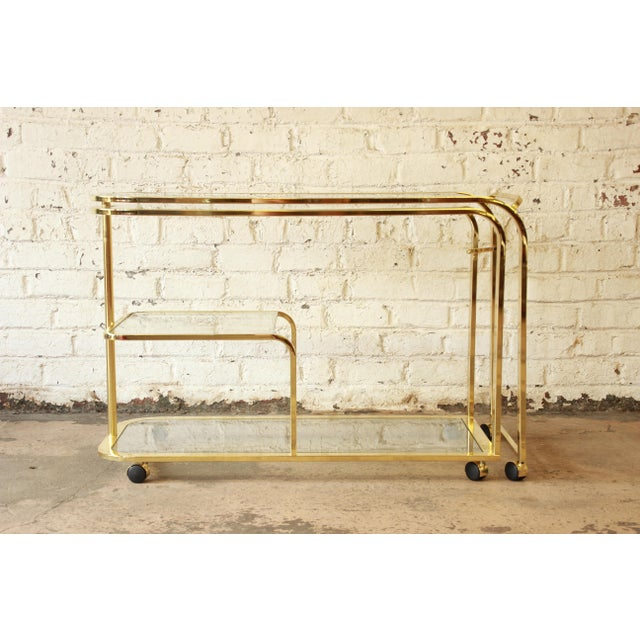 Offering an exceptional brass and glass bar or tea cart designed by Milo Baughman for the Design Institute of America. The...