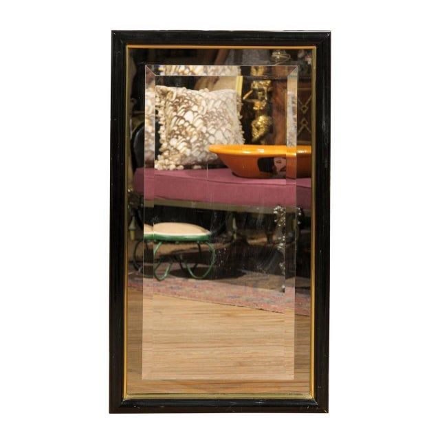 A Mid-Century rectangular black and brass inlaid curved edge frame holding a smoked glass mirror with a beveled mirror...