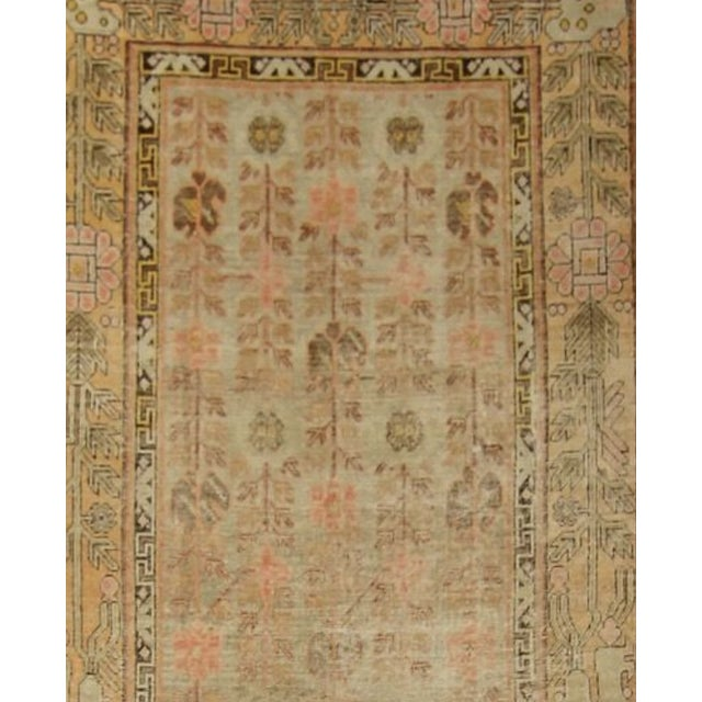 This stunning antique Turkish rug is woven with soft shades of blue, yellow, pink, brown, and green.