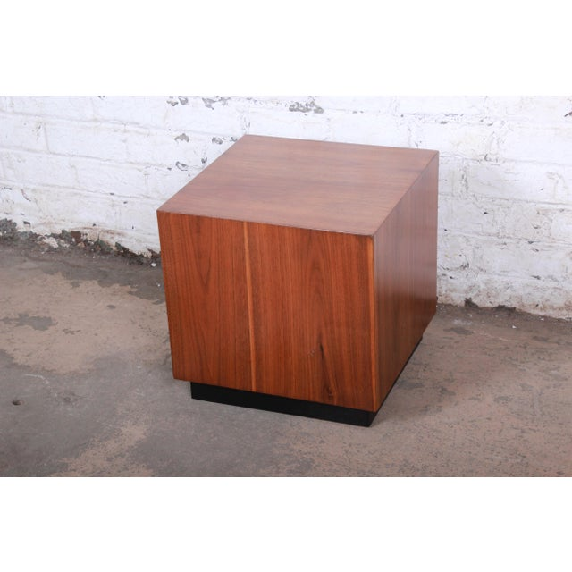 A gorgeous mid-century modern cube side table by Milo Baughman. The table features stunning walnut wood grain and an...