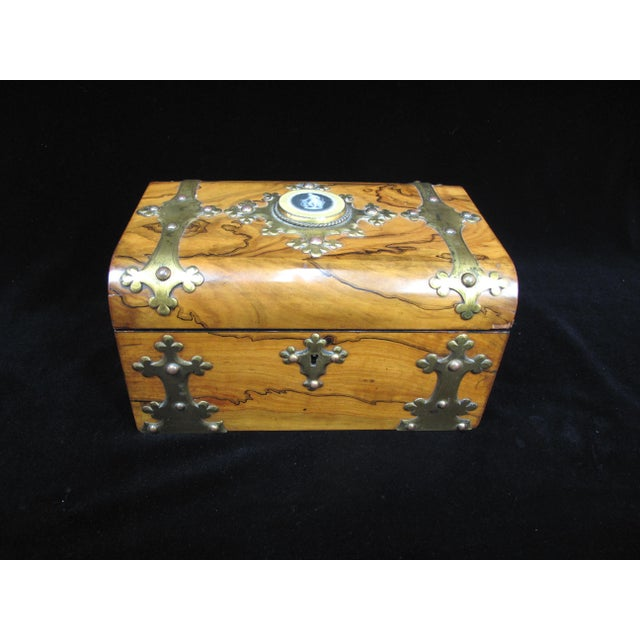 A modest sized box of refined style in Coromandel (an ebony varietal) with reticulated gilded strapping and escutcheon....