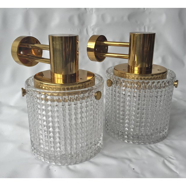A pair of up or down head mounted wall lights, Orrefors attributed, Sweden, circa 1970s. Polished brass and textured...