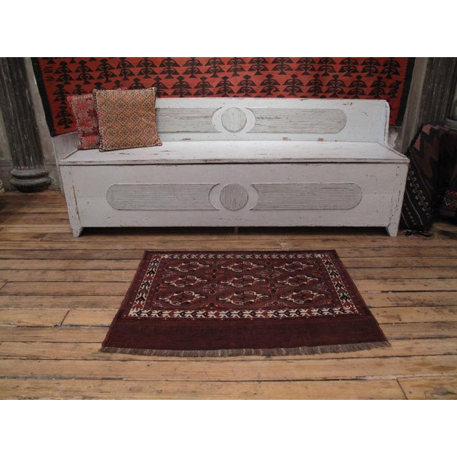 A small pile rug, originally woven as the front of a large bag, typically woven by Turkmen tribes of Central Asia. A...