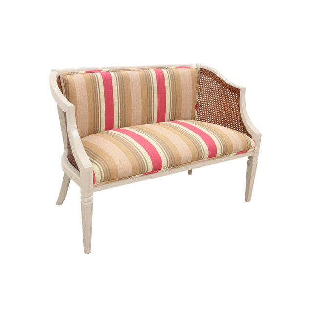 A neoclassical style settee with caned arms. The frame is lacquered in taupe and is supported on squared tapered legs...