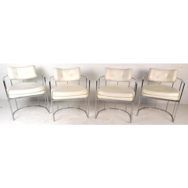 This elegant set of four vintage modern armchairs feature unique ellipse chrome frames that function as arm rests and a...