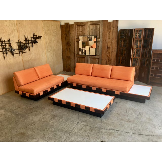 Three piece set with one three seat, one two seat and one coffee table recently recovered in orange micro fiber with white...