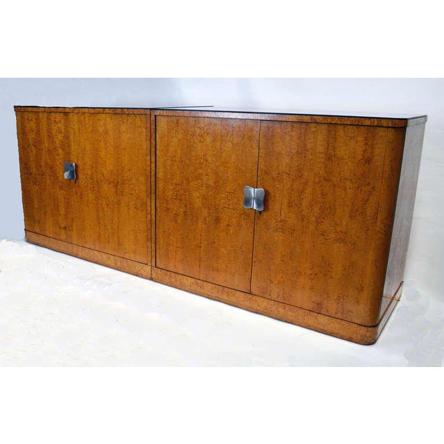 A large pair of bookmatched burl veneer cabinets that form a large buffet. Tops in original black glass. One cabinet with...