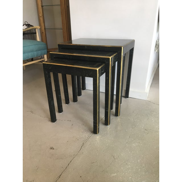 Handsome trio of stone nesting tables with brass inlaid edges. Staggered in height the tables are wonderful for scattering...