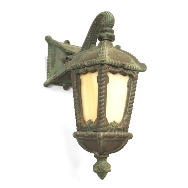 Pair of American Victorian green patinated iron outdoor wall sconce with rope trim and a scroll arm supporting a square...