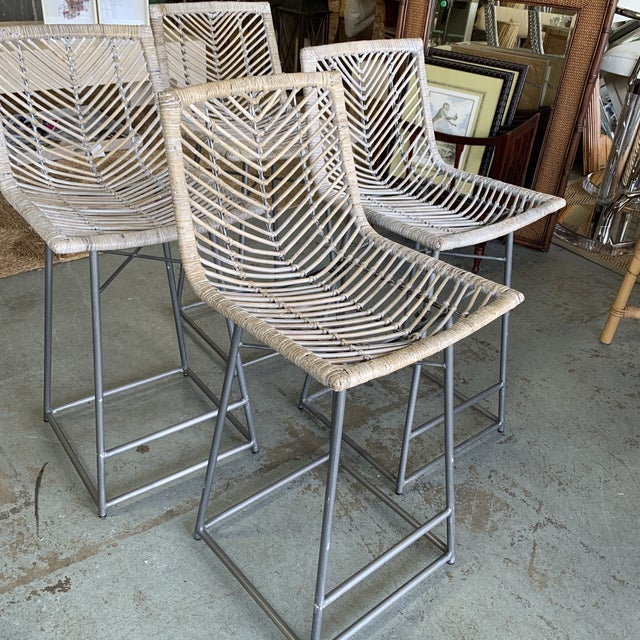 Chic set of 4 of vintage rattan bar stools in a white washed finish with gray base. Please note slightly lower bar stool...