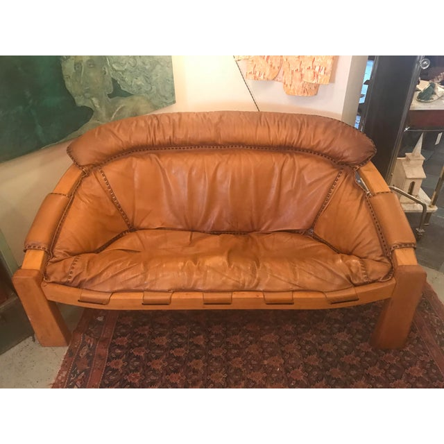 This is a rare and unique midcentury cognac leather sofa with dark brown stitching in the manner of Brazilian designer...