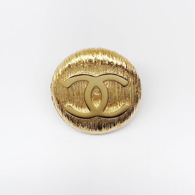 Classic CC logo punch pin by CHANEL. This 24k gold plated button shaped pin adds a couture touch to any lapel, bag, or...