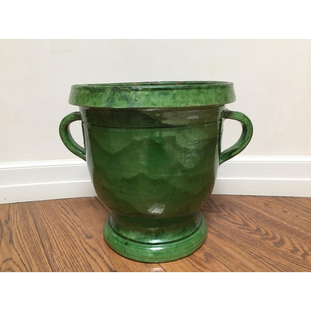 Beautifully hand-glazed in shades of green, terra cotta, French pitcher with handles and footed base. Purchased 20 years...