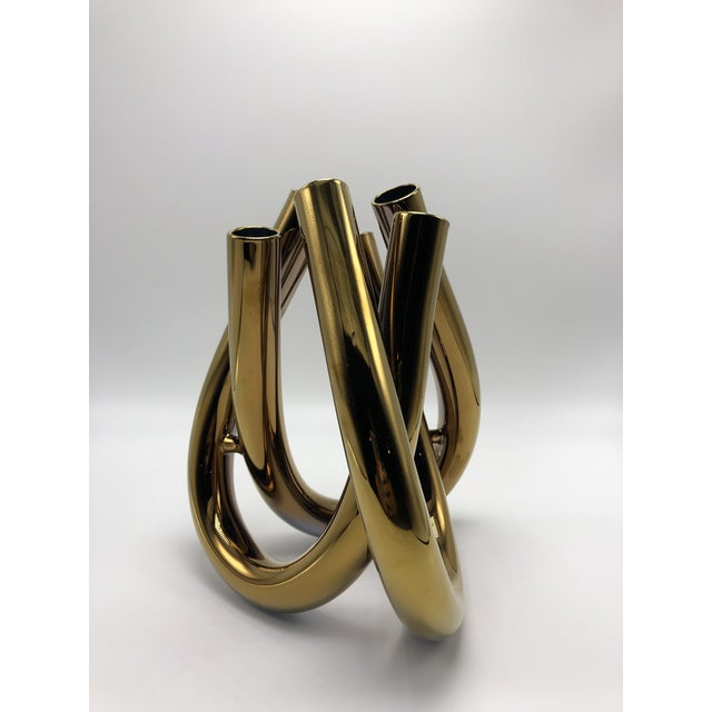 Crafted from glass, this vase is made from three U shaped tubes with six openings.that appear to be intertwined at first...