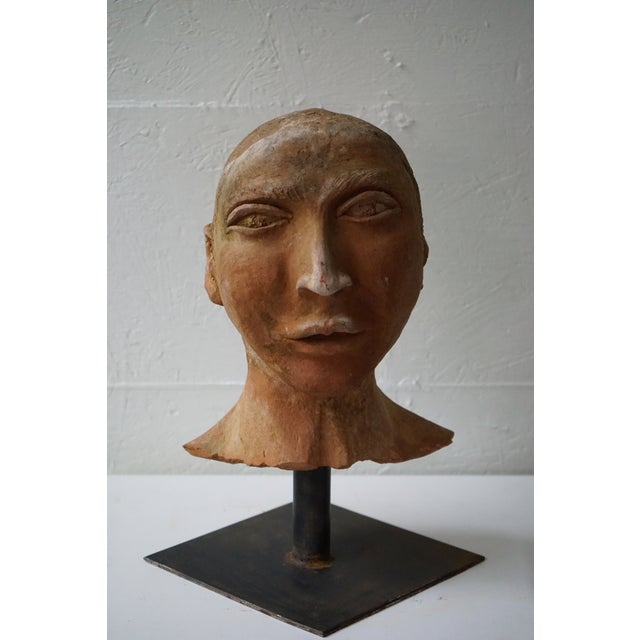 You're looking at a mid-20th century, French, vintage sculpture of a face, made of terra cotta, mounted on a square iron...