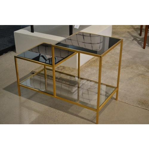 Fabulous vintage end table from France, c.1970. Features a gilt metal frame and three tiered smoked glass shelves. An...