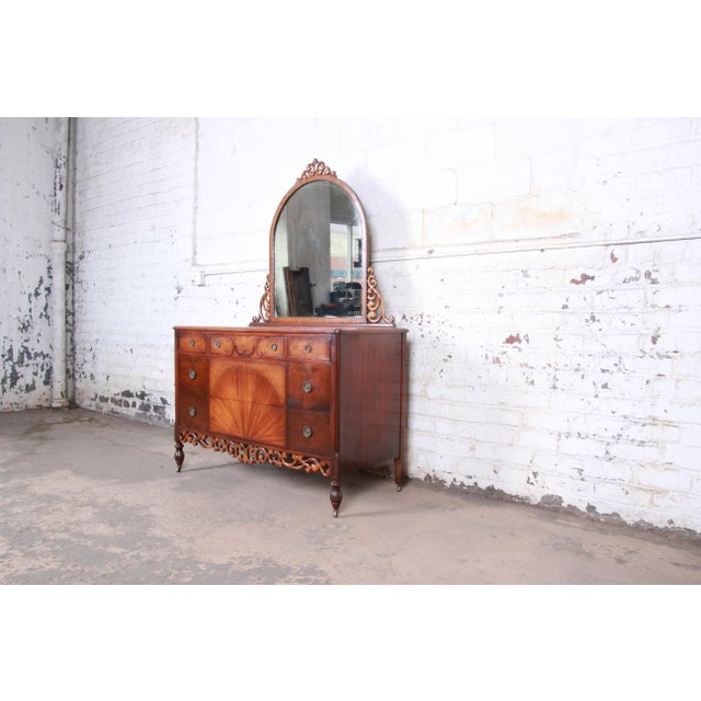 "Antique five-drawer walnut dresser with mirror Early Herman Miller ""All Walnut Line"" USA, circa 1920s Ornately carved with..."