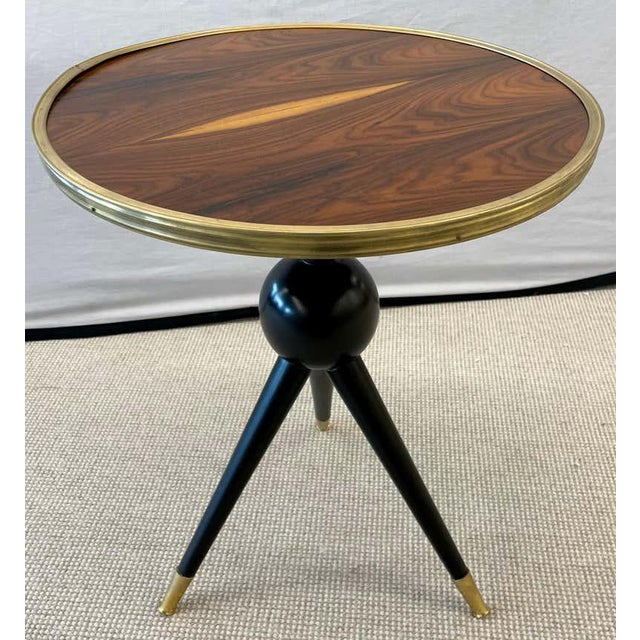 Mid-Century Modern style ebony bronze base and rosewood end table. The brass sabots supporting a tripod ebony base having...