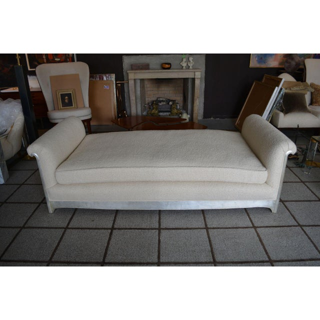 A period Art Deco / Art Moderne daybed in new ivory bouclé upholstery with silver leafed wood frame. Lovely scrolled arms...