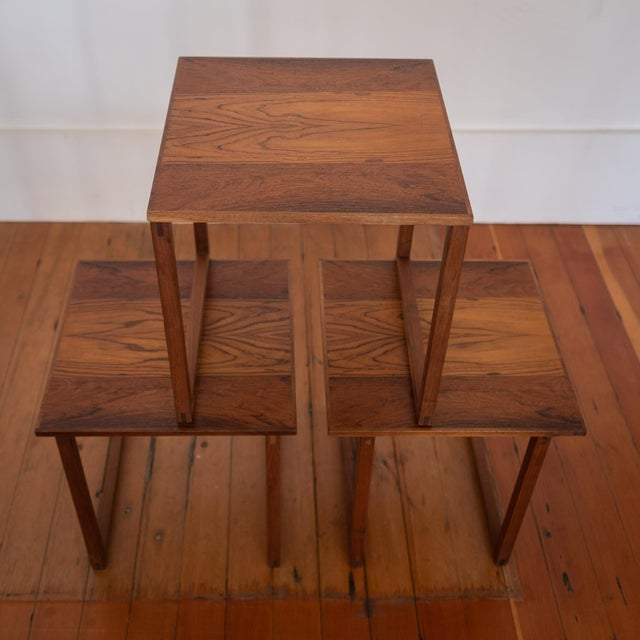 Set of three interlocking nesting tables in rosewood. Beautiful bookmatched rosewood across all three tops. Designed by...