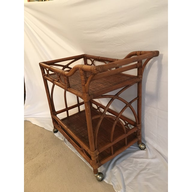 Gorgeous rectangle shaped vintage rattan bar cart with casters. In excellent condition for its age. The frame is on...
