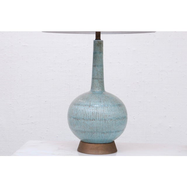 This stylish ceramic lamp features textured reeded lines and a brass base. The light blue color gives it a fresh coastal...