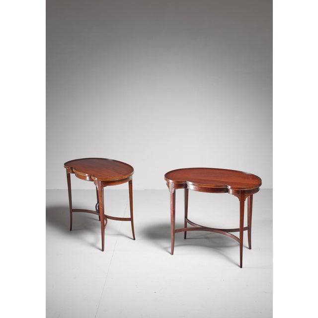 A classic pair of free form mahogany veneer side or tea tables by Nordiska Kompaniet, Sweden. The tables have a metal...