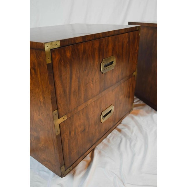 A pair of Campaign style end tables. This pair of end tables feature a rectangular top and conforming case with two...