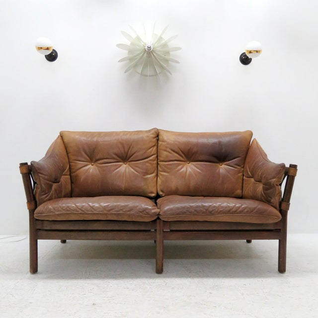 Stunning leather settee designed by Arne Norell in the early 1960s and produced by Norell Möbel AB, Sweden, with thick...