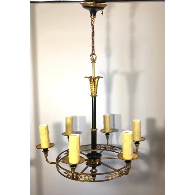 A French Empire Style Chandelier. The gilt circular frame issuing six electrified arms. Each holds an edison base socket...
