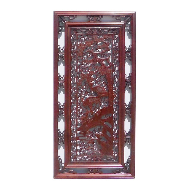 This is a Chinese decorative wood wall panel is stained in a reddish brown color. The vertical rectangular panel has...
