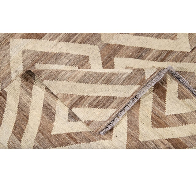 Beautiful hand-knotted wool, contemporary Kilim wool rug. This rug has a beige field with an all-over tan geometric...