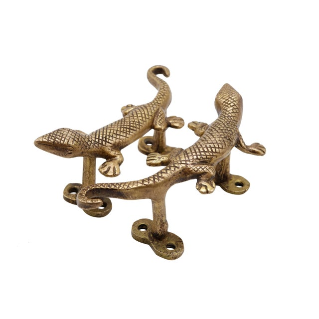 A pair of golden brass lizard door handles or cabinet pulls. Pressed with simple details to convey skin, eyes and toes....