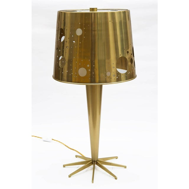 Perforated brass table lamps. Internal lamp shade in white glass and external lampshade in perforated brass. Signed at...