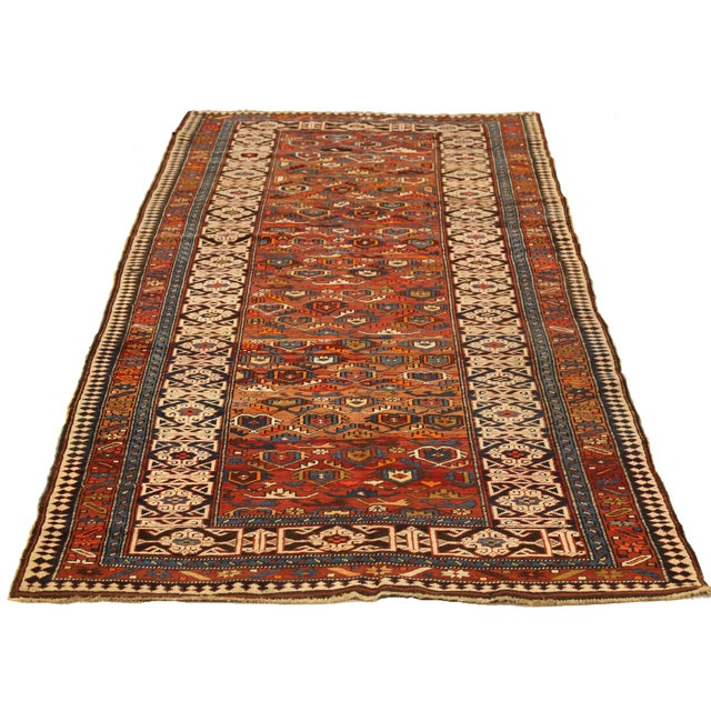 Handmade from fine wool using techniques mastered by ancient shirvan weavers, this antique Persian rug exhibits a classy...