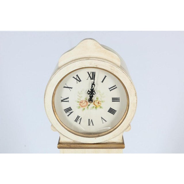 Unique White Wood Grandmother clock with cabinet and shelves. The clock has a white wooden frame with a white finish and...