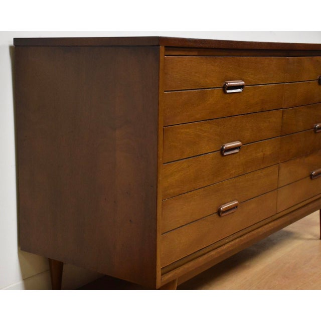 """A mid century modern six drawer dresser on tapered legs and cut out drawer pulls. 54"""" wide. 18"""" deep. 30"""" tall."""