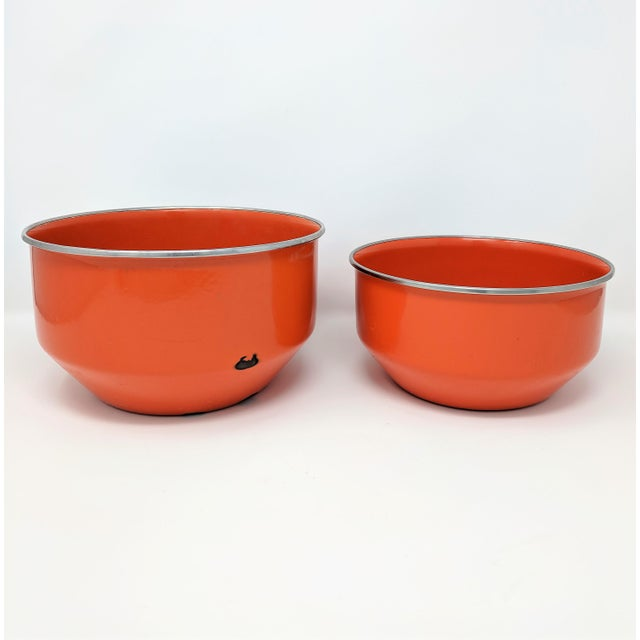 Set of 2 vintage enameled metal nesting bowls. The bowls are a vibrant tomato red, with an unenameled rim.