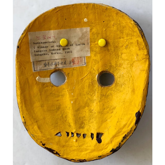 South Korean theatrical mask from Yangchu. Labeled 'Winker or Spirit of Earth' Nunkkumcheki 1965 on the back in both...