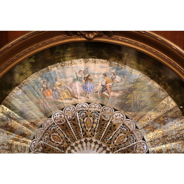 This ornate, antique paper and mother of pearl hand fan was crafted in France, circa 1780. The Rococo style fan is hand...