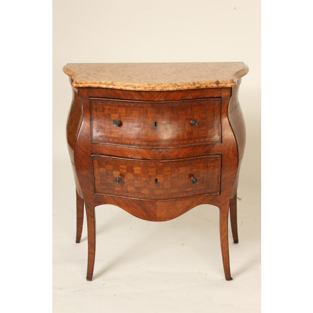 Antique continental Louis XV style parquetry inlaid king wood bombe commode. Features old original marble top. Made in the...