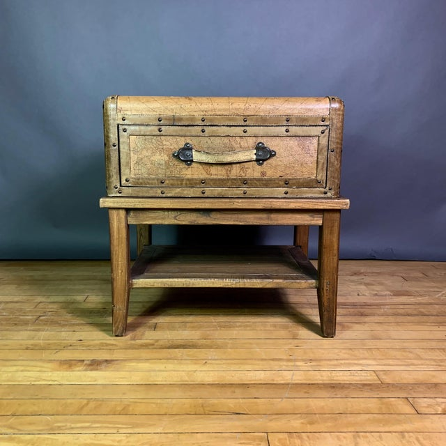 Travel case-form table with top case wrapped in patinated leather printed with earth globe topography on all sides. One...