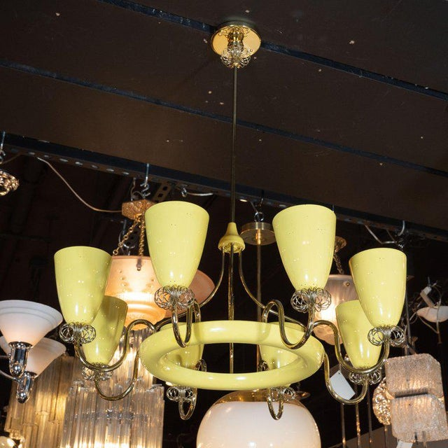 This sophisticated Mid-Century Modern chandelier was realized in France, circa 1950. It features eight conical shades,...