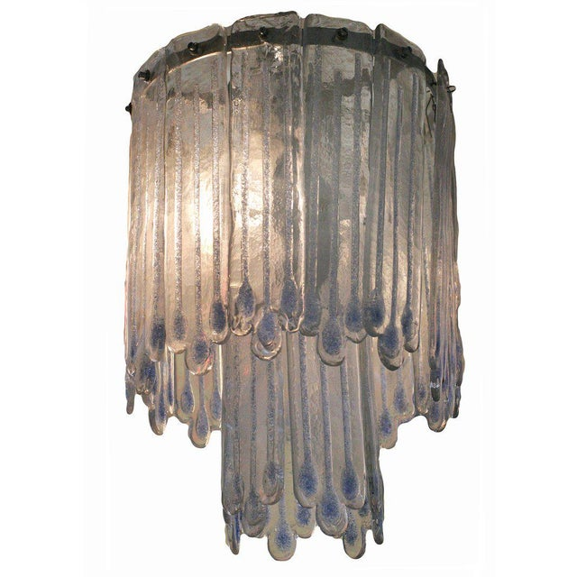 This Mid-Century Modern chandelier attributed to Mazzega features two-tiers of icicle-like opaline Murano glass. Inside...