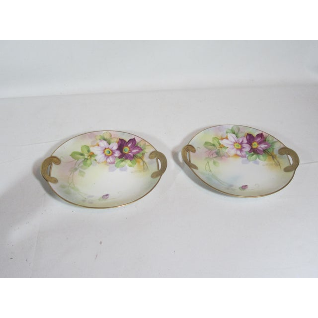 The porcelain plates have a hand painted floral pattern in colors of rose, purple and green with gold trim. They are...