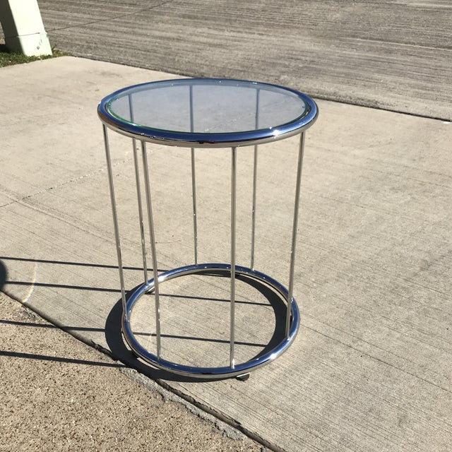 Simple and elegant circular glass top above a stainless steel cage frame side table in the style of Rodolfo Dordoni and...