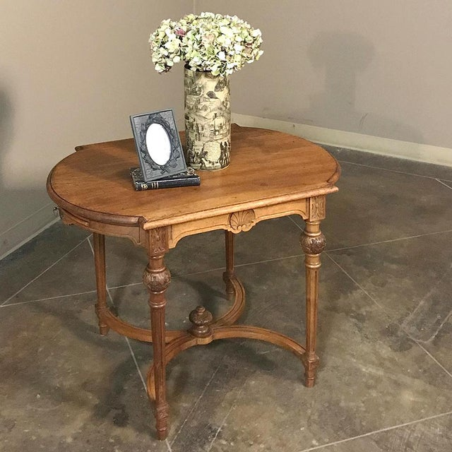 Hand-crafted from fine French walnut, this timeless 19th Century French Neoclassical End Table features rounded ends to...