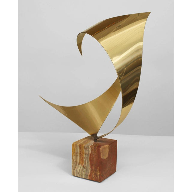 Mid-Century Modern American abstract sculpture of a curved brass form resting upon a cubic onyx base (signed).