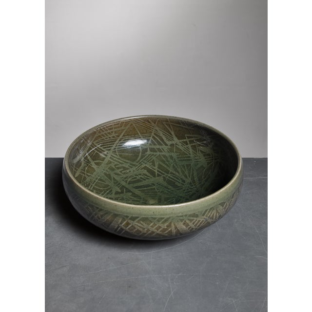 A green ceramic bowl with a wonderful striped motif in the glaze, designed by Nils Thorsson for Royal Copenhagen. Marked...