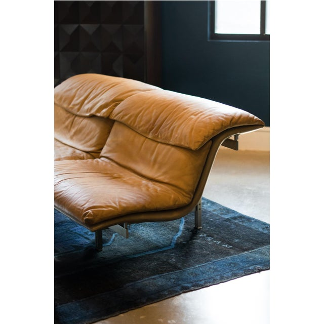 "Giovanni Offredi's leather sofa sports an architectural brushed steel frame and ""Wave"" shaped upholstered seats in cognac..."